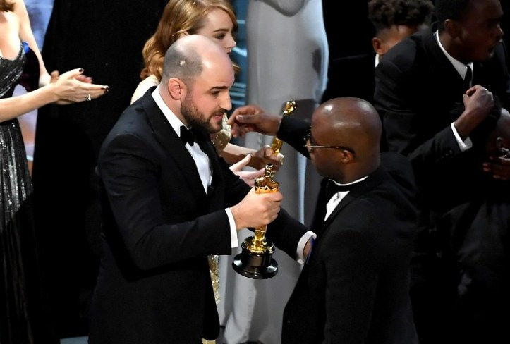 HOLLYWOOD, CA - FEBRUARY 26: ''La La Land' producer Jordan Horowitz (L) hands over the Best Picture award to 'Moonlight' writer/director Barry Jenkins following a presentation error onstage during the 89th Annual Academy Awards at Hollywood & Highland Center on February 26, 2017 in Hollywood, California. Kevin Winter/Getty Images/AFP